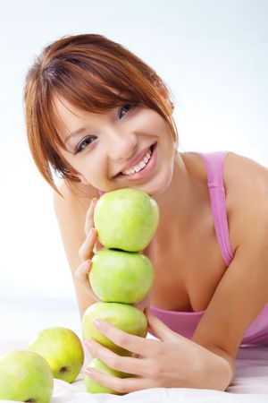 Portrait of cute cheerful teenage girl with green juicy apples photo