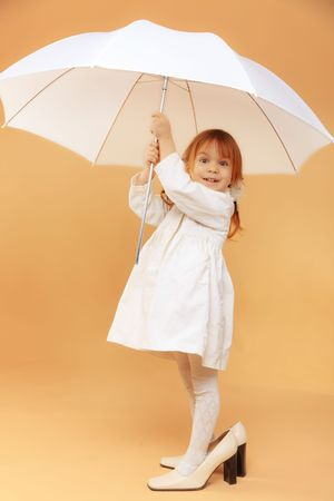 Funny child wearing adult shoes posing with umbrella photo