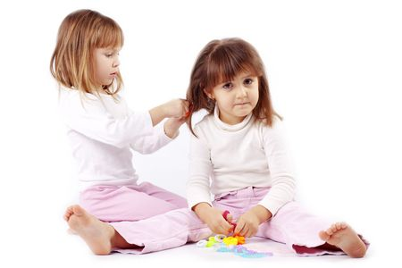 girl action: Two little kid girls playing hairdresser