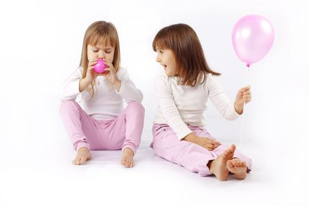 Two little kid girls playing with balloons over white photo