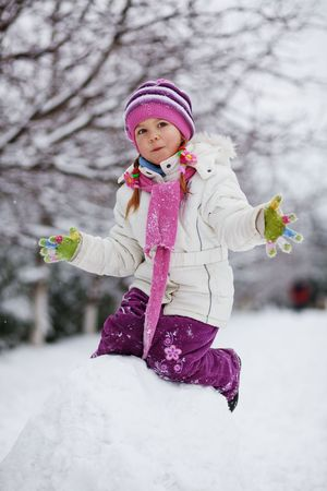 Portrait ov cute little child playing with snow outdoors in winter photo