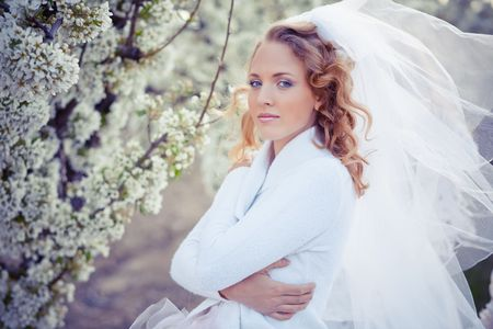 Serene portrait of bride near blossom spring garden in pastel tones photo