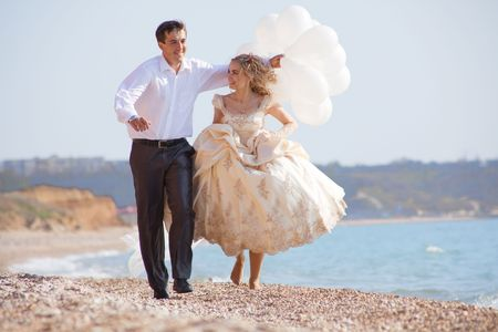 Wedding couple running and kissing on sea coast photo