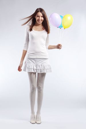 Fashion shot of young beautiful woman holding holiday balloons in her birthday photo