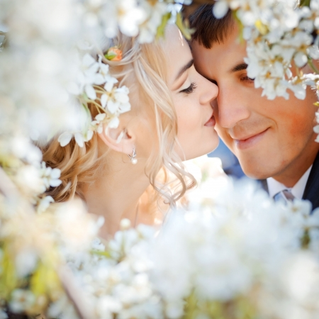 Kissing wedding couple in spring nature close-up portrait photo