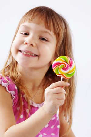 Portrait of funny child eating sweet candy photo