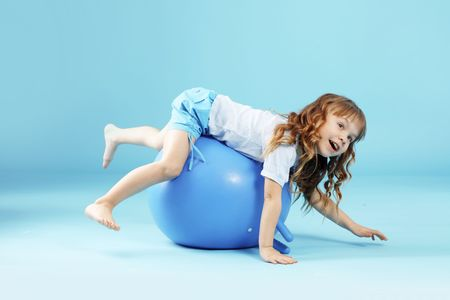 Child with gymnastic ball on bleu studio background