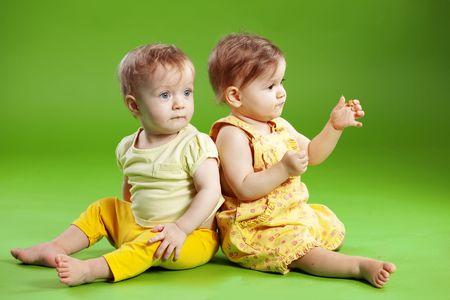 niños sentados: Lindo bebés gemelos sobre verde Foto de archivo