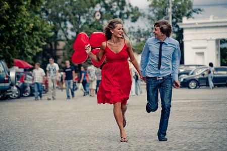 Runnng happy teenage couple in street Stock Photo