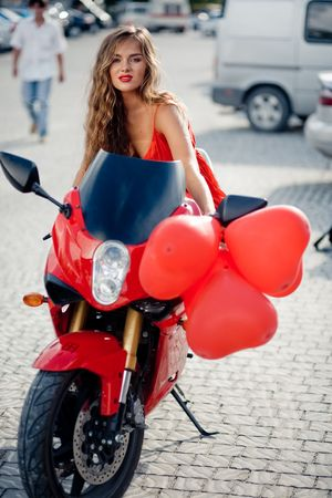 Beautiful woman in red posing on motorcycle photo