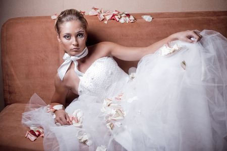 Fashion bride on sofa with sparse rose petals Stock Photo - 6665863