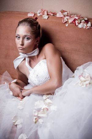 Fashion bride on sofa with sparse rose petals photo