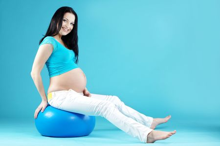 Portrait of pregnant woman on blue photo