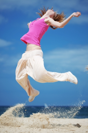 emotional freedom: Teenage girl dancing hip-hop and jumping on beach, summer series Stock Photo