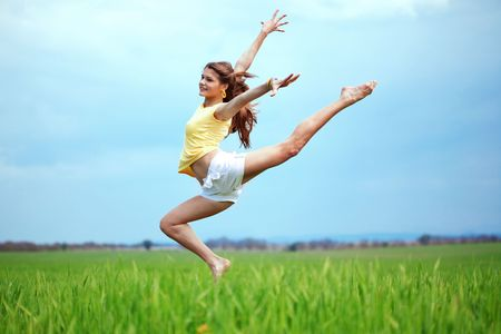 Young beautiful girl doing gymnastic jumps outdoors Stock Photo - 7105617