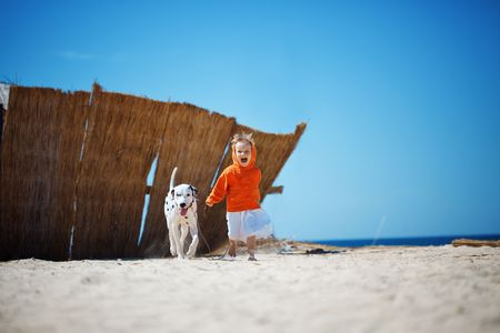 Child walking alone with her lovely dog at beach photo