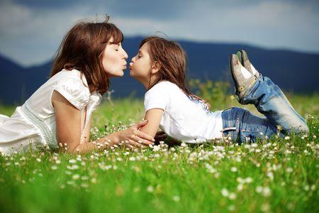 madre e hijos: Madre joven feliz con la hija de descanso al aire libre