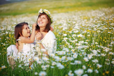 flowers field: Mother with her child playing in camomile field Stock Photo