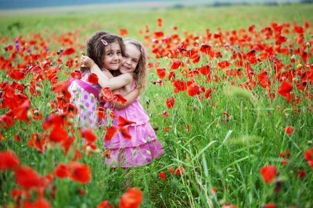 amistad: Ni�os lindos en el campo de la adormidera Foto de archivo