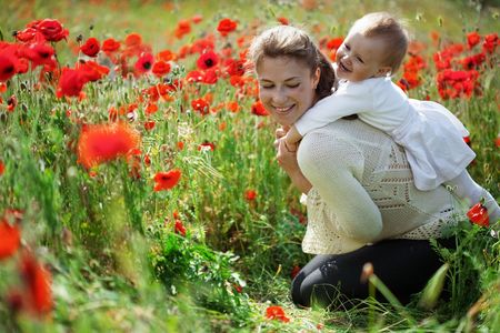 Mother playing with her toddler child in poppy field