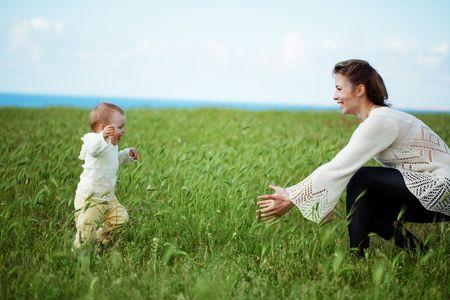playing with baby: Madre a piedi con il suo bambino nel campo verde primavera