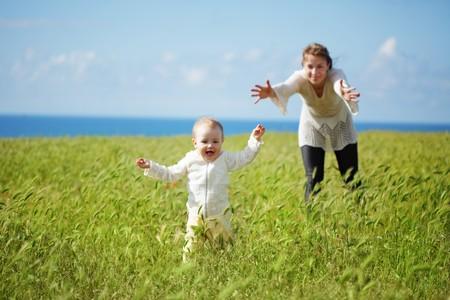 緑のスプリング フィールドで彼女の赤ん坊と歩いて母 写真素材