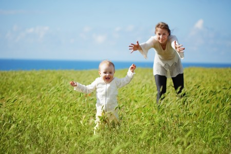naughty girl: Mother walking with her baby in spring green field