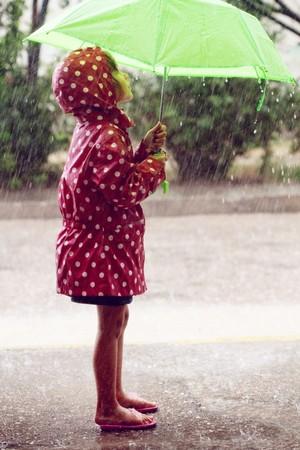 pieds sales: Petit enfant marche sous la pluie.