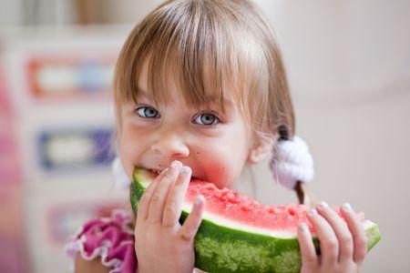 Fauuny child eating watermelon closeup photo