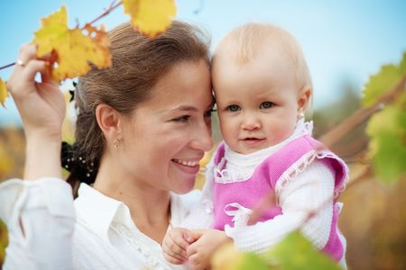 Portrait of loving young mother holding her baby in autumn park photo