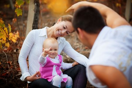 Portrait of loving young parents walking with their baby in autumn park photo