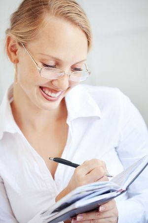 Portrait of a smiling business woman making notes photo