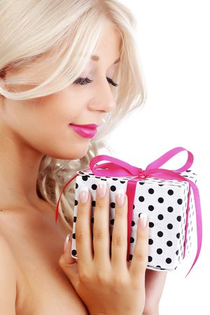 Portrait of cute young woman holding wrapped gift photo