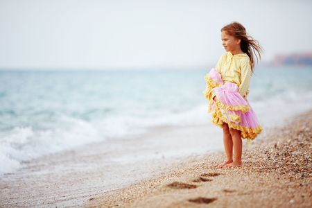 serene people: Little girl playing at the autumn beach Stock Photo