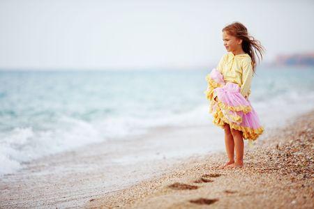klein meisje op strand: Spelen op het herfst strand meisje  Stockfoto