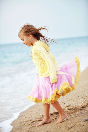 little girl barefoot: Little girl playing at the autumn beach Stock Photo