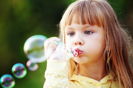 Portrait of funny lovely little girl blowing soap bubbles Stock Photo