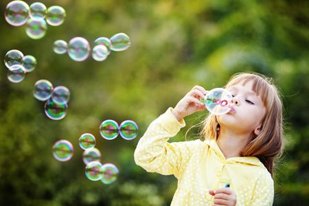 soap bubbles: Portrait of funny lovely little girl blowing soap bubbles Stock Photo