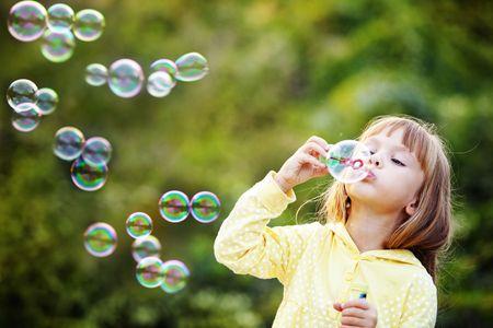 pompas de jabon: Retrato de divertida ni�a encantadora soplando pompas de jab�n