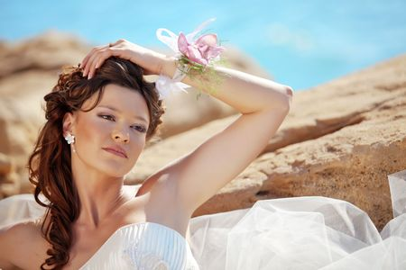 Beautiful bride posing at sea coast photo