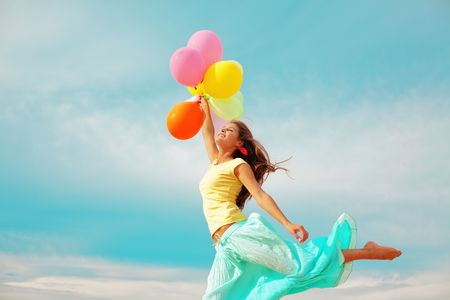 day dream: Happy girl holding bunch of colorful air balloons at the beach