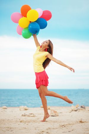 Happy girl holding bunch of colorful air balloons at the beach photo