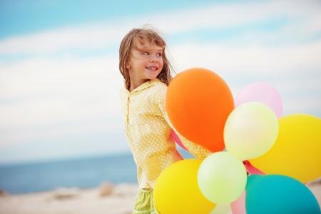niño corriendo: Retrato de niña jugando con globos de aire en la playa
