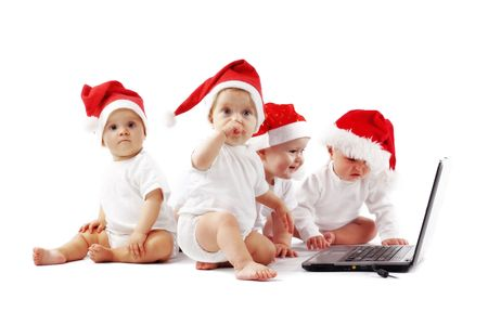 Group of christmas babies playing with laptop Stock Photo