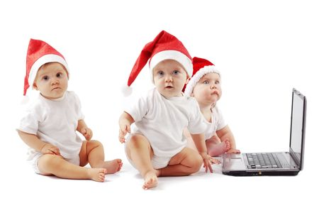 babies playing: Group of christmas babies playing with laptop Stock Photo