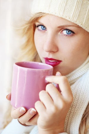 Young beautiful woman wearing winter clothing drinking hot coffee photo