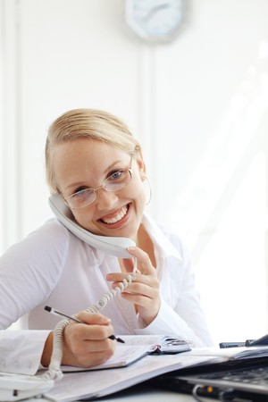 Portrait of a smiling business woman calling by telephone photo
