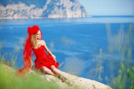 Beautiful bride posing over sea landscape photo