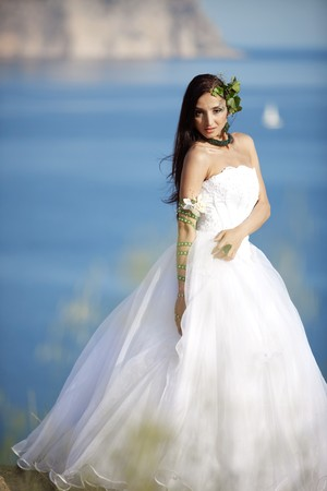 Beautiful bride posing over sea landscape photo