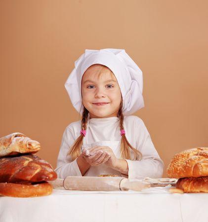 preparing dough: Little cute baker studio shot Stock Photo